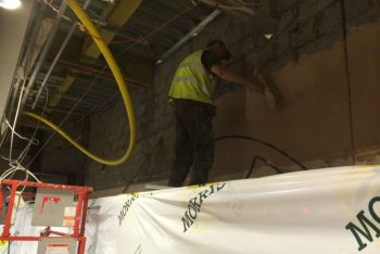 image of plasterer applying solid plaster to block wall