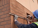 Image showing brick effect being cut into coloured render
