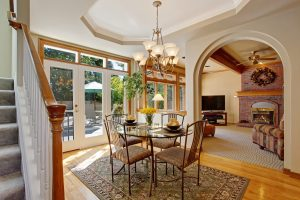 image of a dining room with plaster arches through to living room